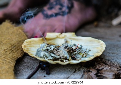 horizontal photo of burning white sage incense with stream of smoke in a sea shell, background of woman's foot with mandala tattoo