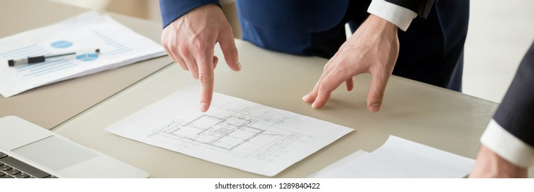Horizontal photo businessman and architect negotiating, close up hand points on paper project plan building, construction industry and pricing of real estate concept, banner for website header design