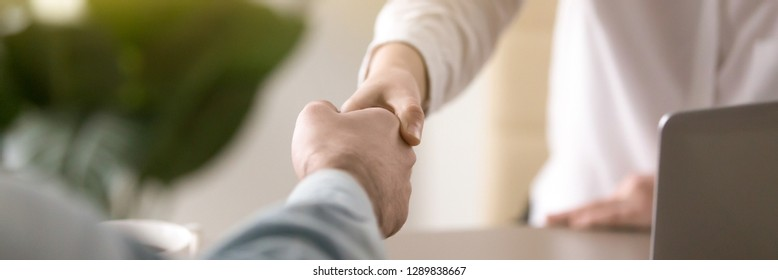 Horizontal photo businesspeople shaking hands, greeting or farewell at business negotiations, client and company representative handshaking, symbol gesture of respect banner for website header design