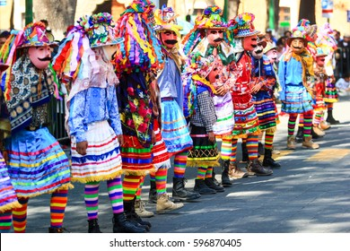 Horizontal photo of a Carnival scene, dancers wearing a traditional mexican folk costume and mask rich in color