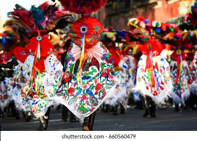 Horizontal photo of a Carnival scene, dancers wearing a traditional mexican folk with an amazing cape rich in color