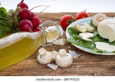 Horizontal photo of Champignons and various vegetable radishes, tomatoes) with coarse-grained salt around plus bottle with lemonade. All is on wooden table.