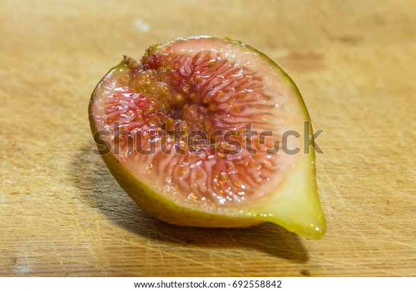 Horizontal photo of a close up on a half of a cut fig on a wooden cutting board