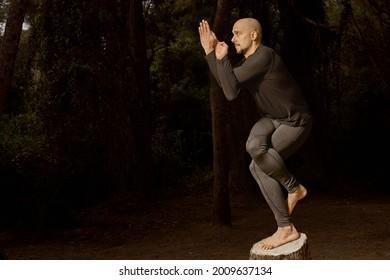Foto horizontal con espacio de copia. Hombre calvo latino vestido con ropa oscura, profesor de yoga practicando sobre un tronco en el bosque