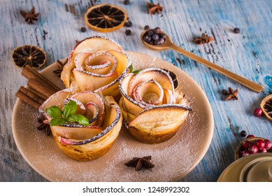 Horizontal photo with crispy dessert. Sweet is made from apple slices and puff pastry. Dessert is called apple roses. Several herbs and spices are spilled around with powder sugar.