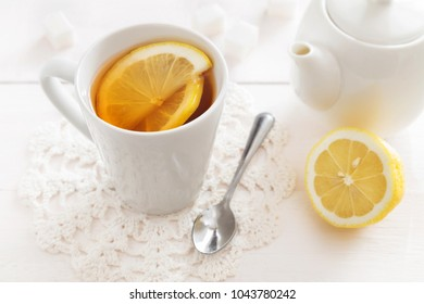 Horizontal photo of a cup of lemon tea and a teapot