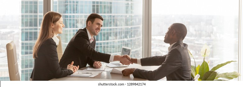 Horizontal photo diverse businesspeople gather at modern office boardroom, black boss congratulate partner make deal effective negotiations signing agreement concept, banner for website header design
