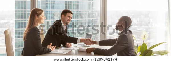 Horizontal photo diverse businesspeople gather at modern office boardroom, black boss congratulate partner make deal effective negotiations signing agreement concept, banner for website header design