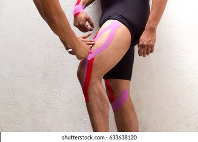 Horizontal photo of a doctor physiotherapist applying kinesio taping on the left thigh of a male cyclist