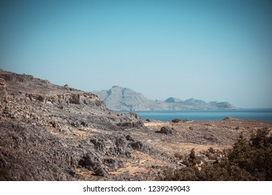 Horizontal photo with dry rocks covered just by stones. Rocks are brown and grey. Rocks are next to famous town Lindos on Rhodes island. Sky and sea are blue.