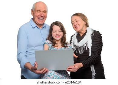 Horizontal photo of family enjoying internet jokes. Grandparents and their child using notebook and laughing at funny viral pictures.