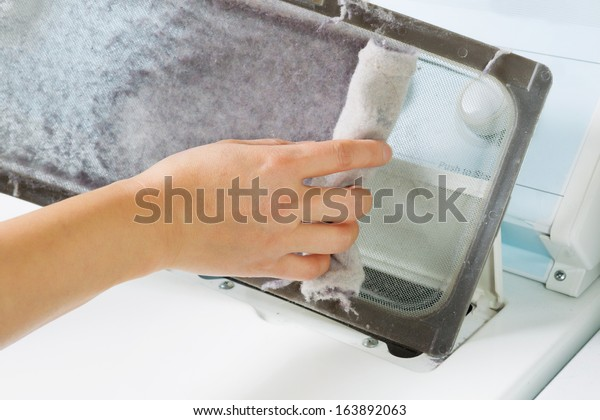 Horizontal photo of female hand taking the lint out from dirty air filter of the dyer machine