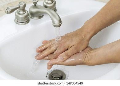 Horizontal photo of female hands finishing cleanup with running water and bathroom sink in background