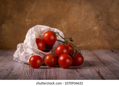 Horizontal photo with few twigs full of small red cherry tomatoes. Vegetable is placed in worn crumpled paper bag. Food is on wooden board with white and brown color.