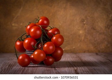 Horizontal photo with few twigs full of small red cherry tomatoes. Vegetable is placed in worn vintage can. Tin is on wooden board with white and brown color. Background is textured.