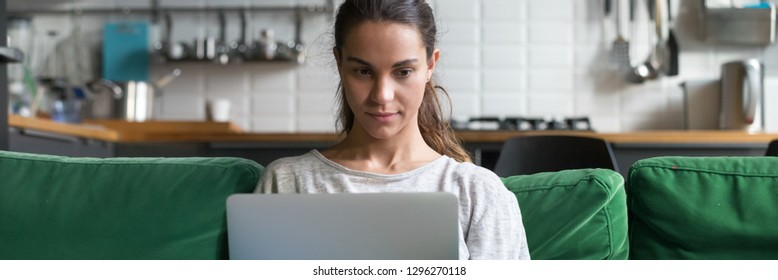 Horizontal photo focused mixed race woman sitting on couch at home using working on laptop reading news check email communicate online concept banner for website header design with copy space for text