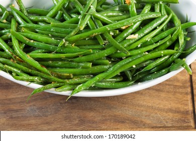 Horizontal photo of freshly cooked green beans in white bowl on black walnut serving board