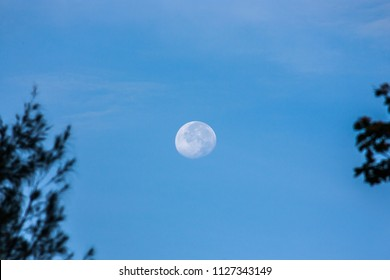 Horizontal photo of full moon captured during the daytime with blue sky background in Thailand. The moon is bright enough to appear during the daytime.