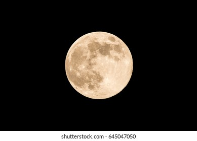 Horizontal photo of full moon. Moon with nice soft yellow color. Visible craters on the edge of space body. The bright and light areas on surface are clearly visible. Space around is black.