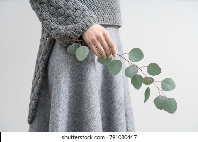 Horizontal photo of a girl in a gray knitted pullover and a skirt on the light gray background in the studio. She holds an eucalyptus branch in the right hand. Closeup.