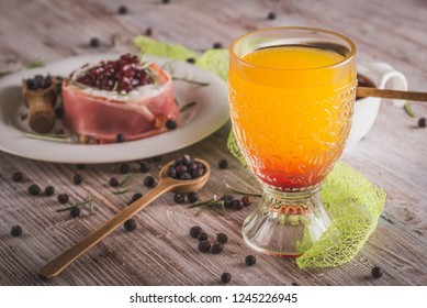 Horizontal photo of glass with orange juice which has red grenadine syrup on bottom. Wrapped cheese in dry ham with cranberries on top is with glass on white plate with spilled juniper.