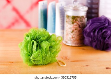 Horizontal photo green bath sponge on light wooden board with few bath accessories and pink sea salt in glass jar in background in front of red wall.
