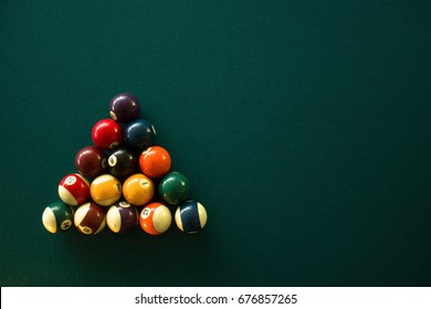 Horizontal photo of a green billiard table and billiard balls view from above