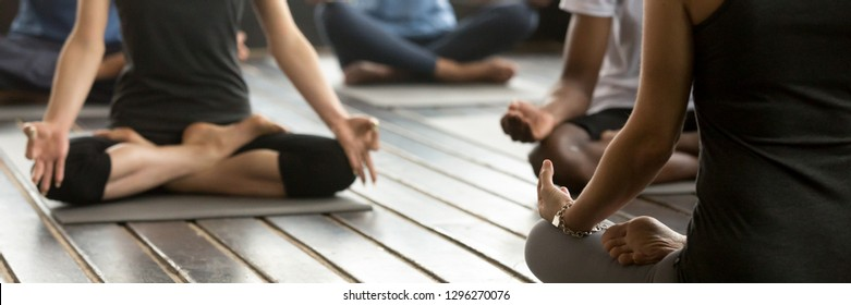 Horizontal photo group people wearing activewear sporty girls guys at training workout sitting on mats practicing yoga Easy Seat position meditating feels good concept banner for website header design