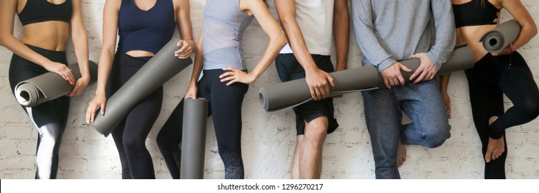 Horizontal photo group young sporty people wearing activewear holding yoga mats standing near wall before or after training, healthcare and active lifestyle concept, banner for website header design