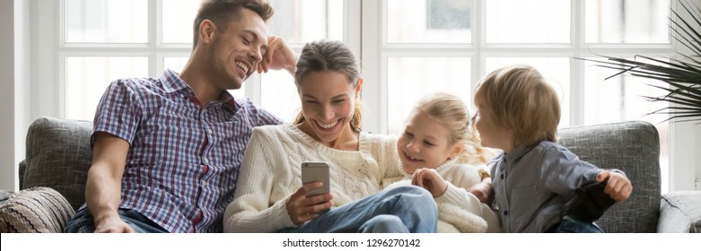 Horizontal photo happy family with little kids watching funny video on phone sitting on couch enjoy weekend at home, modern tech leisure activities free time concept, banner for website header design