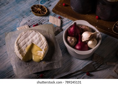 Horizontal photo of hot melted camembert cheese on paper sheet with bowl full of garlic and onions and old vintage cans on blue worn wooden board. Dried lemon rings are spilled around.