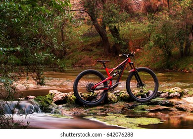 Horizontal photo of an isolated full suspension mountain bike standing in the  river stream in a beautiful forest