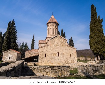 Horizontal photo of Khvtaeba (Holy Spirit) church at Ikalto monastery and ruins in front of it in Kakheti, Republic of Georgia, Caucasus, in the early morning, at sunrise. Blue sky in the background.