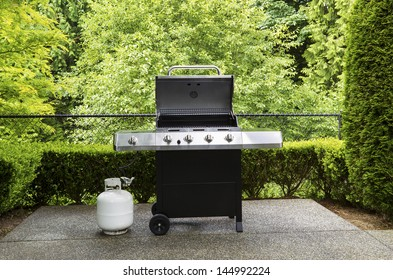 Horizontal photo of large barbeque cooker, with lid up, on concrete outdoor patio with woods background