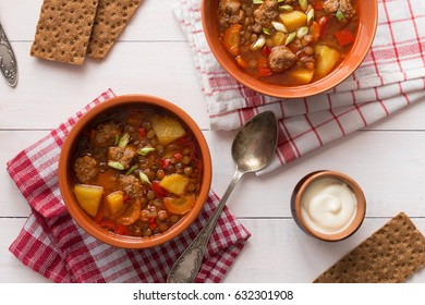 Horizontal photo of lentil soup with meatballs and pepper