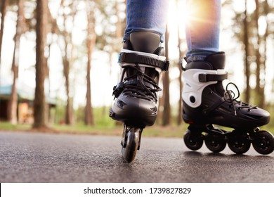 Horizontal photo of modern black roller skates being on road outskirts, unknown person riding during weekends, enjoying leisure activities, being fond of active lifestyle. Rollerblading concept.