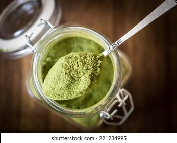 Horizontal photo of moringa powder (moringa is consider to be superfood) on a silver spoon placed over a small glass jar full of moringa powder. Wooden background. Close up.