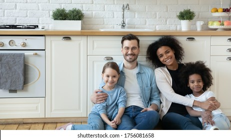 Horizontal photo multiracial excited couple with adorable daughters sit in modern renovated kitchen on warm floor smile look at camera. New property owners, happy multicultural family portrait concept