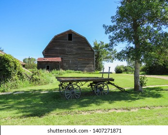 A horizontal photo of a old barn and a old hay wagon at a old homestead.