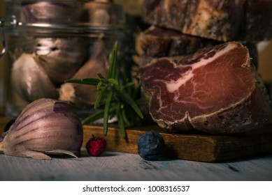 Horizontal photo of pork meat from wild boar which is dried and smoked. The pieces are stacked. Italian and tuscany traditional food. Garlic, berries and rosemary on vintage wooden board.