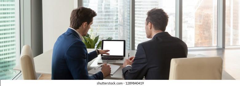 Horizontal photo rear back businessman sitting at desk points on laptop screen empty mock up copyspace analyse market company development. Internship mentoring concept banner for website header design