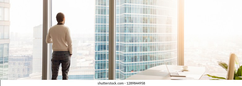Horizontal photo rear back successful businessman look through window at big city, rest has break, think about future business vision concept, banner for website header design with copy space for text