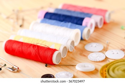 Horizontal photo with set of tailoring threads which are placed in a queue on light wooden board with other accessories around.