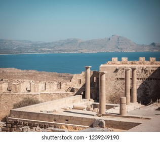 Horizontal photo with several pillars of Lindos Acropolis. Acropolys is on Rhodes island in Mediterranean Sea. Sea and sky is blue. Few rocks and hills are visible in background.