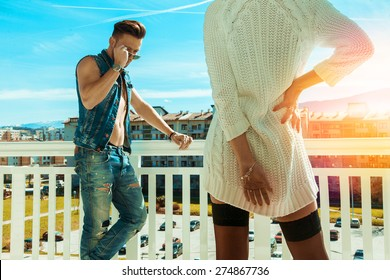 Horizontal photo of sexy fashionable man and seduce woman backside on balcony