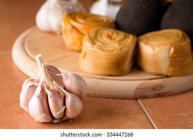 Horizontal photo with single garlic bud placed on ceramic tiles in front of wooden plate with rolled smoked cheese and other vegetable.