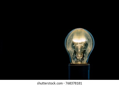 Horizontal photo of single glass bulb placed in the socket on black background. The fire and flame inside is caused by burning wire. The bright smoke is filling the inner space. Edge of object is blue