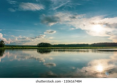 Horizontal photo with summer landscape. Small pond is in foreground with reflected blue evening sky full of dramatic clouds. Green meadow with trees is in background.