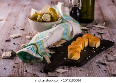 Horizontal photo of traditional rolled parenica cheese. Cheese is placed on vintage wooden board with spilled spice and salt around next to checkered towel or stuffed green peppers.