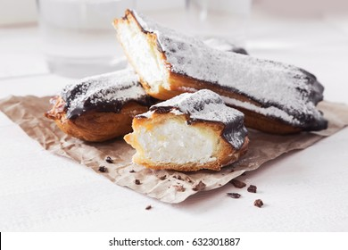 A horizontal photo of two chocolate eclairs filled with cream